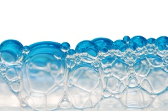 Blue foam bubbles isolated on white.